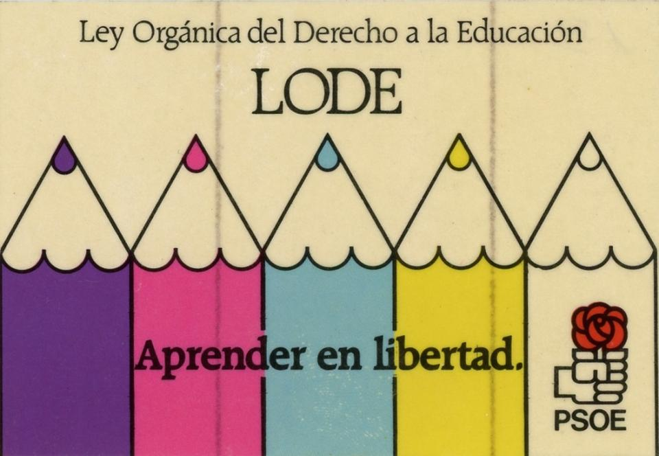 The sticker shows the tips of five color pencils coming up from the bottom up in the colors (left to right): purple, pink, blue, yellow and white. On the bottom right hand corner there is the logo for the Partido Socialista Obrero Español (PSOE), which is a sideways fist holding a red flower. The sticker is advocating for the right to education.